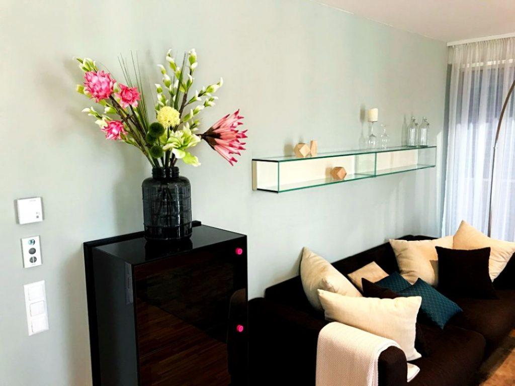 Wohnzimmerwand in Grün mit Kommode und Kunstblumen